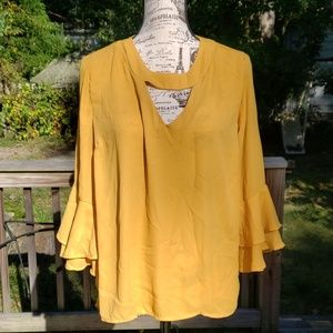 Mustard colored shirt with ruffled sleeves